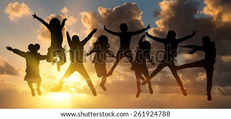 Group of children jumping outdoors against the sun - stock photo