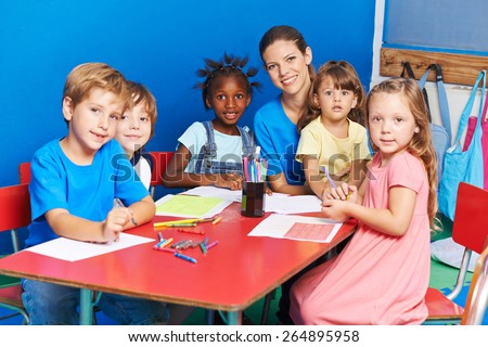 Group of children painting on table with nursery teacher in a kindergarten - stock photo