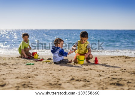 Group of Children Playing with Beach Toys under Sunlight - stock photo