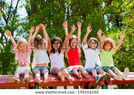 Group of children raising hands together in park. - stock photo