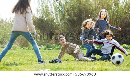 Group of children running after ball in spring park