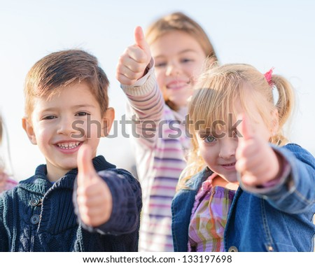 Group Of Children Showing Thumb Up Sign, Outdoors - stock photo