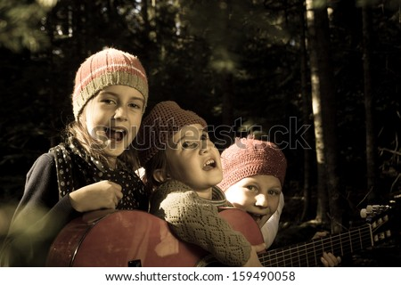 Group of children singing and playing guitar together in the forest - stock photo