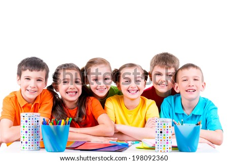 Group of children sitting at a table with markers, crayons and colored cardboard. - stock photo