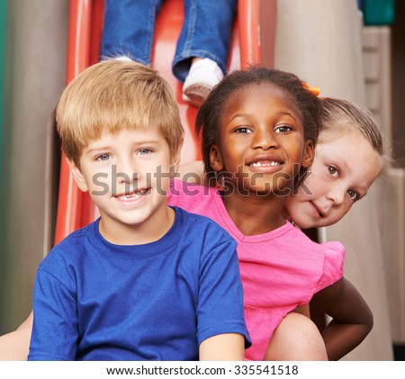 Group of children sitting behind each other on a slide in kindergarten - stock photo
