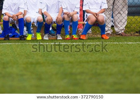 Group Of Children Soccer Team on Training. Youth Young Soccer Football Team on a Soccer Sport Field. Group of Boys Soccer Players Sitting Together and Supporting. Reserve players on a soccer bench. - stock photo