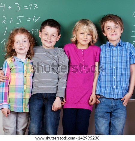 Group of children standing in front of panel at the classroom