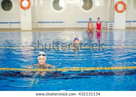 Group of children training in swimming pool - stock photo