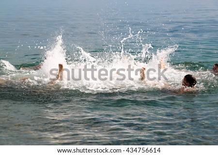 Group of children upside down splashing in the sea. - stock photo
