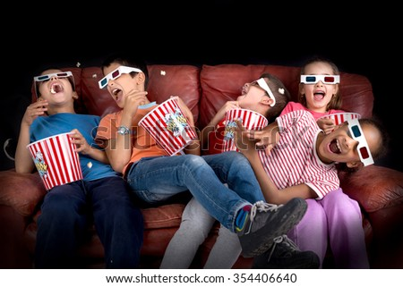 Group of children with 3d glasses and popcorn in a sofa having fun - stock photo