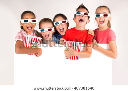 Group of children with 3d glasses and popcorn over a white board - stock photo