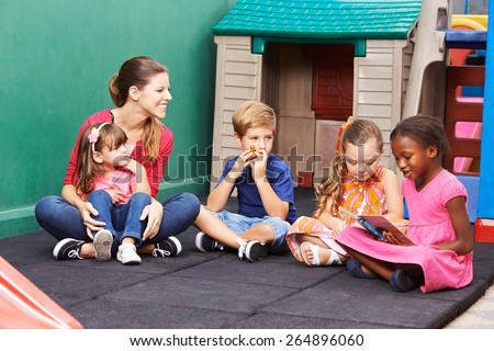 Group of children with nursery teacher reading a book in preschool - stock photo