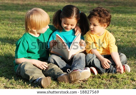 Group of children with the book on a grass in park with the book - stock photo