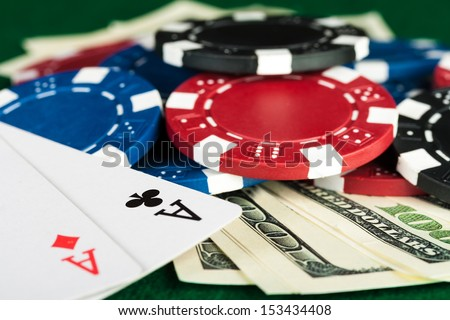 Group of chips, money and poker cards on the green cloth. - stock photo