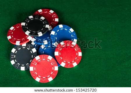 Group of chips on the green cloth. - stock photo
