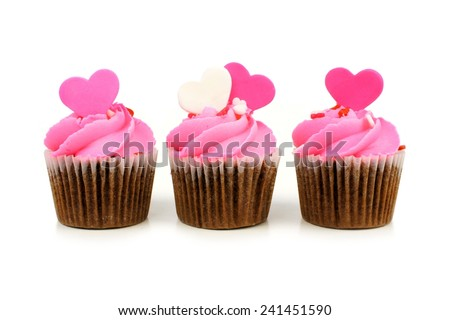 Group of chocolate Valentines Day cupcakes with pink frosting and heart toppers over white