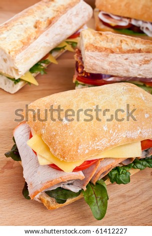 group of ciabatta and baguette  sandwiches stuffed with meat, cheese and vegetables on a wooden table - stock photo