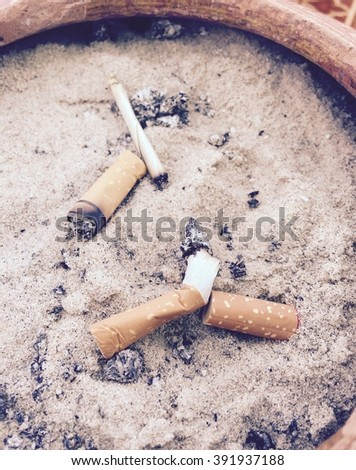 Group of cigarette in ashtray with sand, quitting smoking conceptual. Cigarette butts.vintage tone picture style. - stock photo