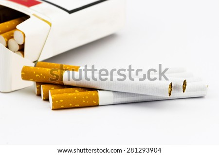Group of cigarettes lying near the box full of cigarettes isolated on white background - stock photo