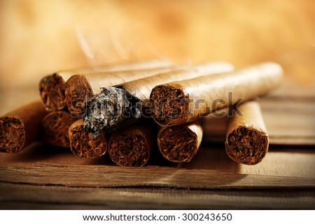 Group of cigars and burning one on wooden table on brown background - stock photo
