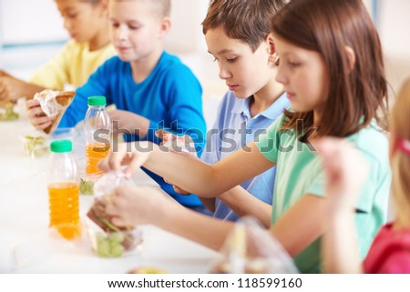 Group of classmates having lunch during break - stock photo