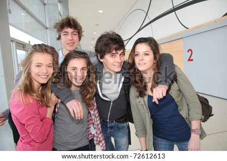Group of classmates standing in school entrance hall - stock photo