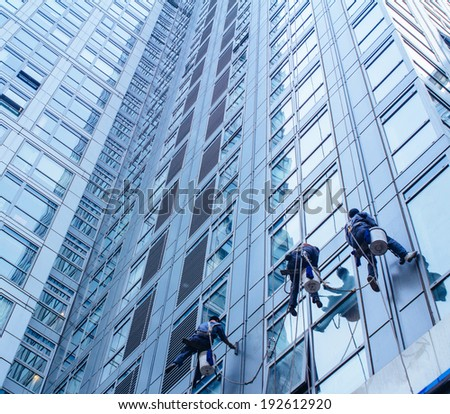 Group of Cleaners are cleaning windows of a office building - stock photo