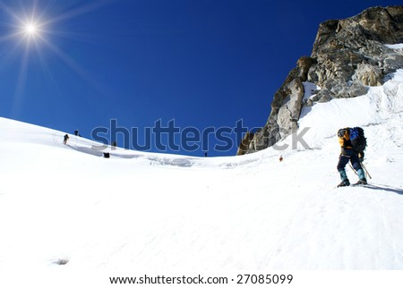 Group of climbers goes out on the top of mountain - stock photo