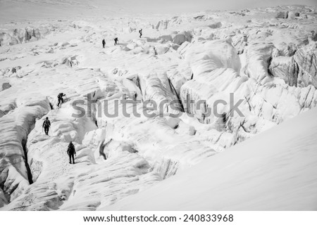 Group of climbers on a glacier with many crevasses - stock photo