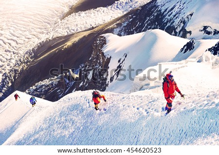 Group of climbers reaches the summit of mountain peak. Climbing and mountaineering sport concept,.