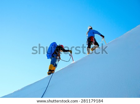 Group of climbers reaches the top of a snowy mountain