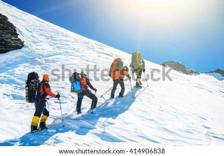 Group of climbers reaching the simmit. Team work concept - stock photo