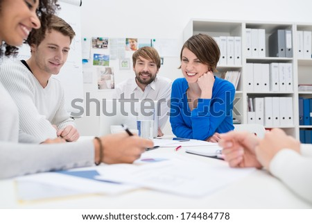 Group of co-workers having a brainstorming session sitting around a table together in the office as they plan their business strategy - stock photo