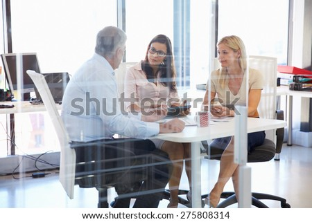 Group of colleagues meeting around a table in an office - stock photo