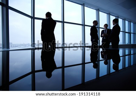 Group of colleagues standing against window in office and speaking - stock photo