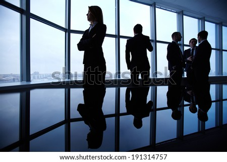 Group of colleagues standing along window in office