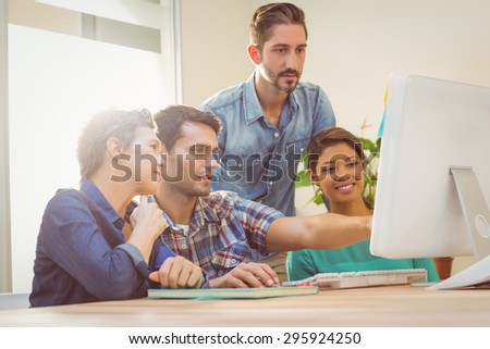Group of colleagues using laptop at office - stock photo