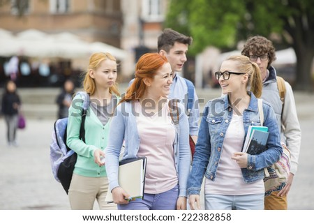 Group of college friends walking outdoors - stock photo