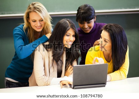 group of college students discussing project on laptop in classroom