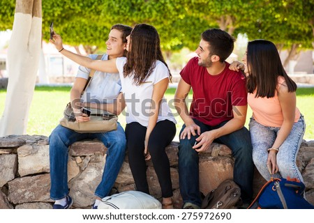 Group of college students hanging out at school and taking a selfie with a smartphone