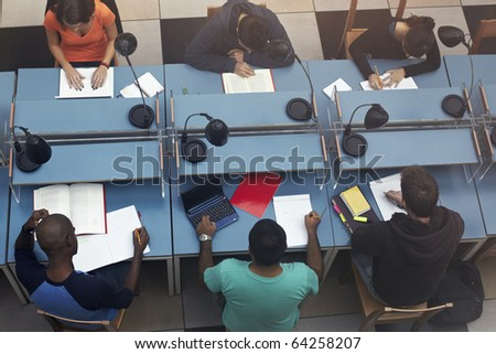 group of college students sitting on desks in library. Horizontal shape, high angle view - stock photo