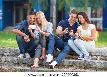 Group of college students sitting outdoors using mobile phones - stock photo