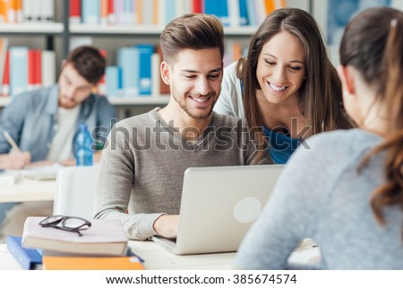 Group of college students studying in the school library, a girl and a boy are using a laptop and connecting to internet