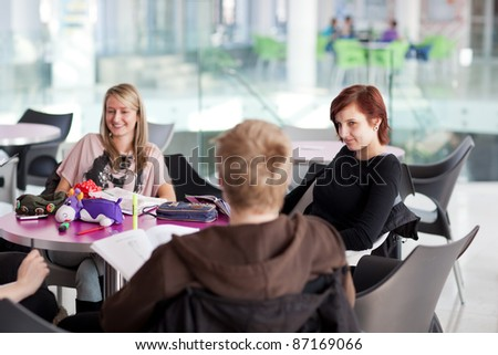 Group of college/university students during a brake between classes - chatting, comparing notes, having fun (shallow DOF; color toned image) - stock photo
