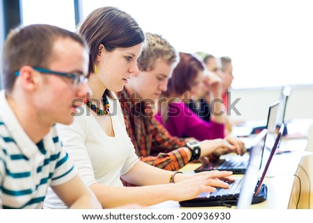 Group of college/university students in in a classroom during class (shallow DOF, color toned image) - stock photo