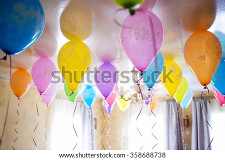 Group of colorful balloons on white ceiling - stock photo