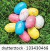 Group of colorful candy robin eggs on green moss - stock photo