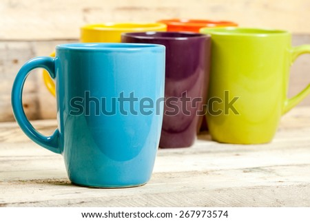Group of colorful cups on wooden background. - stock photo