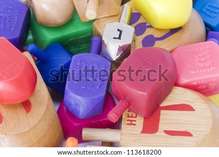 Group of colorful dreidles. Dreidle is a traditional game for the Jewish holiday of Chanukah. Shown is an assortment of wood and plastic dreidles, and one silver colored dreidle. - stock photo