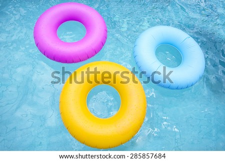 Group of colorful inflatable tubes floating in a swimming pool - stock photo